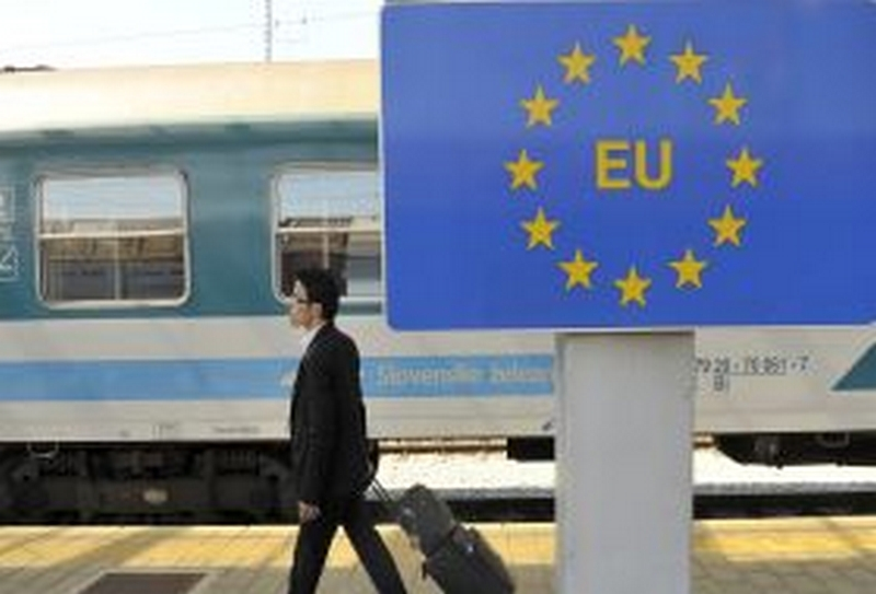 A passenger walks past a European Union sign at the border cross with Croatia in Dobova