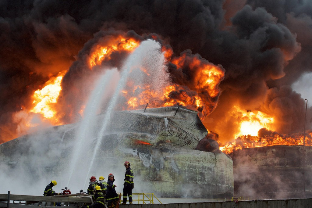 (150407) -- GULEI, April 7, 2015 (Xinhua) -- Firefighters try to extinguish fire at the site of a chemical plant blast in Zhangzhou, southeast China's Fujian Province, April 7, 2015. A xylene facility leaked oil and caught fire, which led to blasts and a fire at three nearby oil storage tanks at Tenglong Aromatic Hydrocarbon (Zhangzhou) Co. Ltd. on the Gulei Peninsula in Zhangzhou City at 6:56 p.m. (1056GMT) on Monday. Six people were injured in the plant blast. (Xinhua/Jiang Kehong) (lfj)